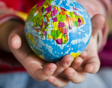 Image of a child's hand holding a globe